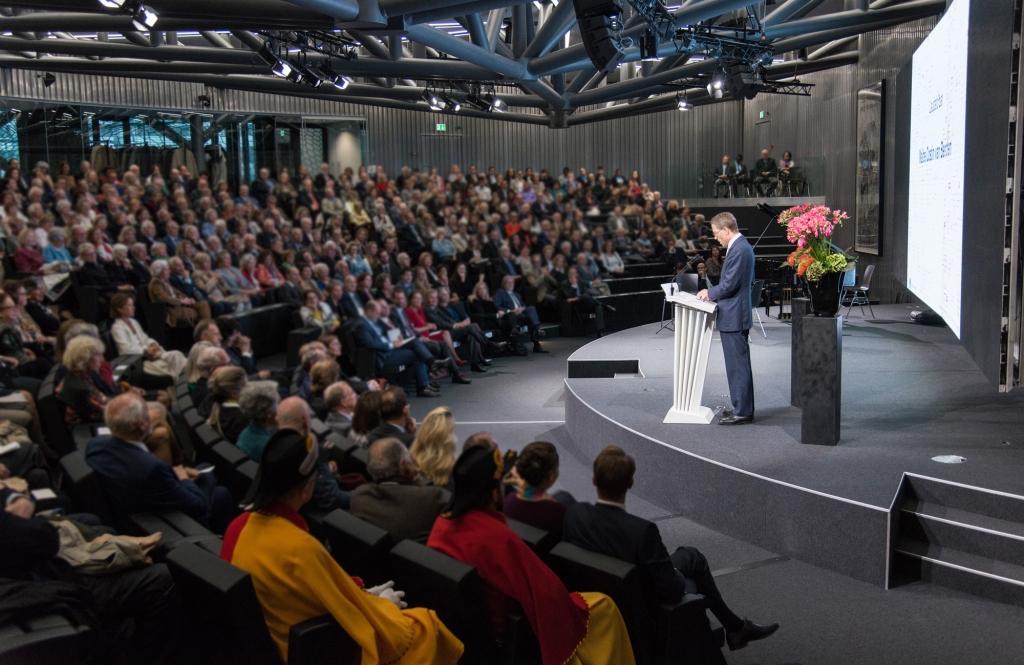 Un homme qui fait un discours sur une estrade devant un public